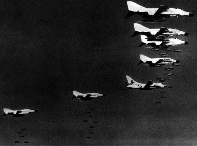 McDonnell Douglas F-4C Phantom IIs in formation flight dropping bombs.