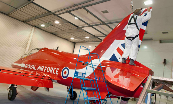A member of the RAF Cranwell Paint Bay Team putting people's names of Red Arrows Hawk Jet XX322