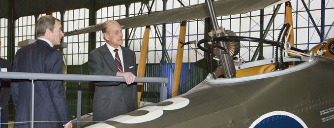 The Duke of Edinburgh looking into the cockpit of a Royal Aircraft Factory R.E.8