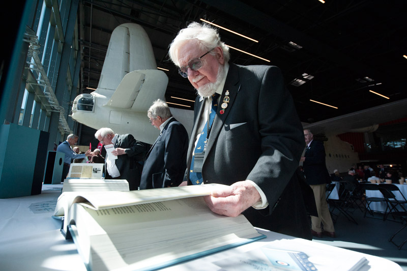 RAF Veterans looking at copies of the RAF Centenary Anthology