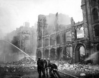Firemen at work in a bomb-damaged street in London
